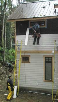 Eddie and Shawn putting siding on the back of the house