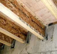 Wooden I-beams connected to the basement wall.